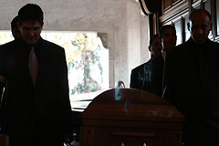 Handsome pallbearers enter with coffin.